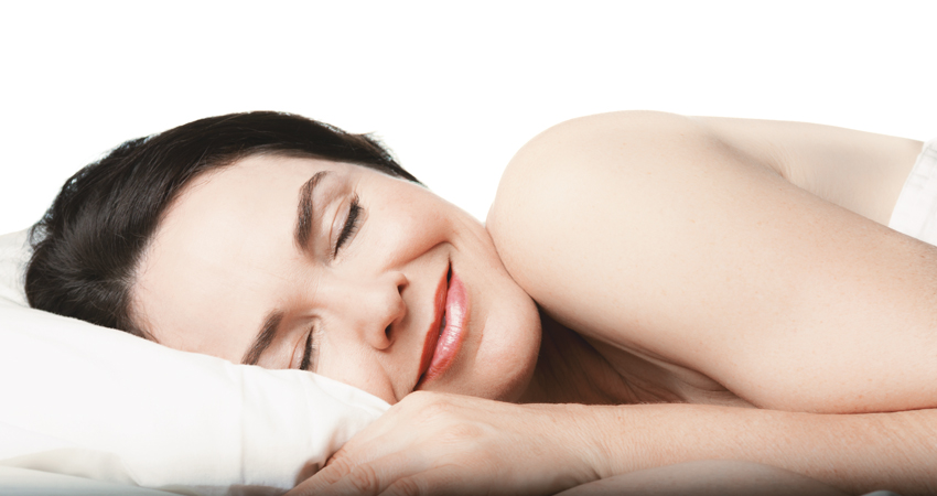 Woman smiles while enjoying a restful sleep thanks to nightguard